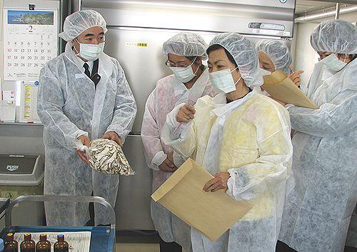 輸入食品の検査室で説明を受けるせこゆき子、八田ひろ子氏ら=名古屋検疫所