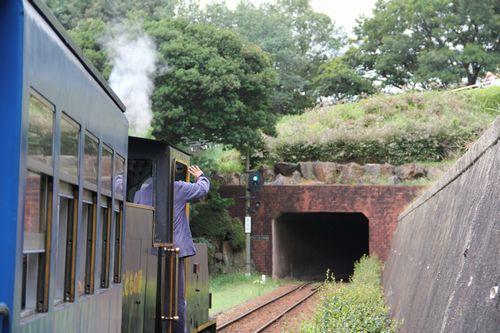 煙を吐きトンネルに入る子ども汽車。機関士が子どもたちに手を振る