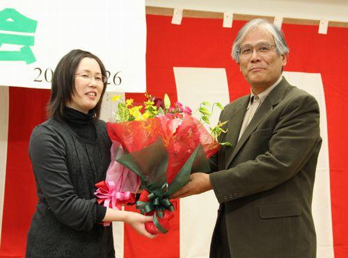 勝利報告会で祝福される、小池克則さんの妻で原告の小池友子さん(左)=11月26日、名古屋市