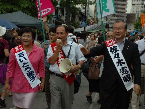 覚王山日泰寺の縁日で参拝客に後期高齢者医療制度廃止を訴えるさいとう愛子さん(左)と佐々木憲昭衆院議員(右)