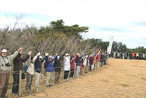 ヘリ訓練場を「人間の鎖」で包囲し訓練場反対を訴える人たち=15日、田原市・大山山頂