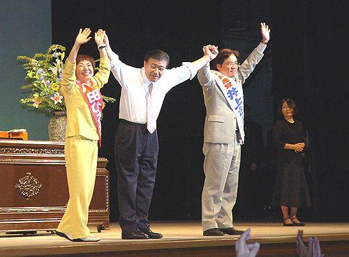 会場を埋め尽くした参加者からの声援にこたえる(左から)八田前参院議員、市田書記局長、井上参院議員=7日夜、名古屋市公会堂ホール
